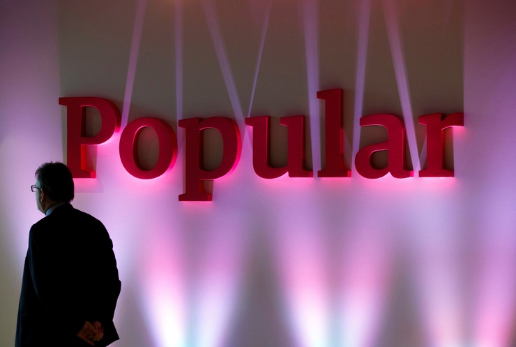 FILE PHOTO: A man casetas next to the logo of Spain's Banco Popular during the b